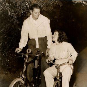 Johnny Weissmuller rides a bike,Lupe Vélez rides a trike.