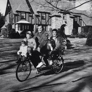 Linda Lee Boone, Cheryl Lynn Boone, Pat Boone, Laura Gene Boone, Shirley Lee Boone and Debby Boone ride a bike.