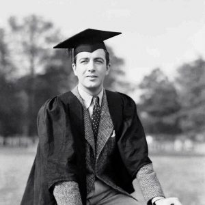 Robert Taylor graduates on a bike. (And smokes a cigarette while he's at it.)