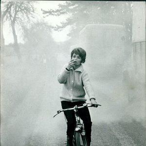 Pascale Petit rides a bike, smokes a cigarette.