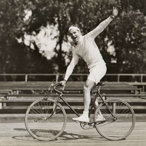 Neil Hamilton rides a bike.Neil Hamilton, motion picture actor and bicycle enthusiast, will ride his bicycle 400 miles, from Los Angeles to San Francisco, on a Good Will Tour in behalf of the Olympic Games, to be held in Los Angeles July 30 to August 16.– Press Release, May, 1932