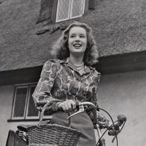 Sally Ann Howes rides a bike.