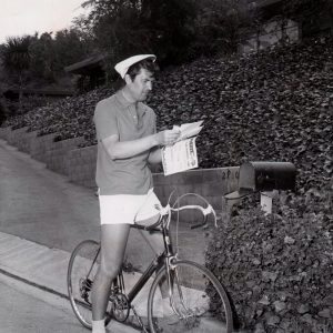 Fess Parker rides a bike, reads his mail.