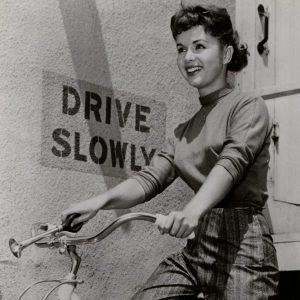 Debbie Reynolds rides a bike, honks a horn.