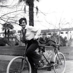 Nancy Carroll rides a tandem, solo.