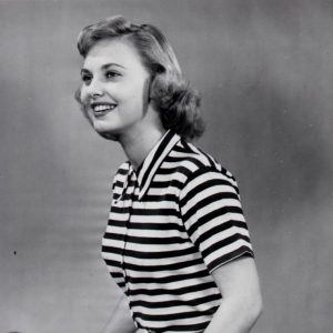 "Lola Albright models a bike, and models bike clothes.""IDEAL FOR CYCLING– At home with shorts, slacks or pedal-pushers, this versatile cotton T-shirt is done in brilliant green-and-white stripes. It has short sleeves and buttons up to a neat turn-down collar. Actress LOLA ALBRIGHT likes it for cycling."" – Acme News, March 23, 1949"