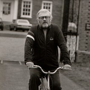 Edward Woodward rides a bike.