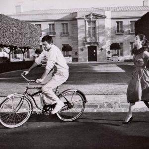 Jerry Lewis rides a bike. Anna Maria Alberghetti pursues.