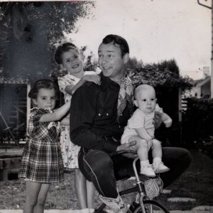 Cheryl Rogers, Roy Rogers and Roy Rogers, Jr., ride a trike. Linda Rogers hangs on.