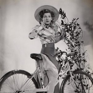 Constance Moore rides a bike, catches her skirt.