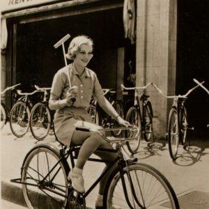 Muriel Evans rides a bike, wields a mallet.