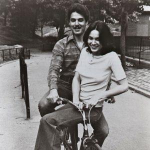 Chris Sarandon and Cristina Raines ride a bike.