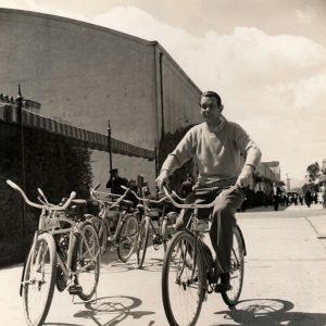 Raymond Massey rides a bike.