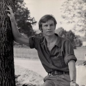 Michael York rides a bike, holds a tree.