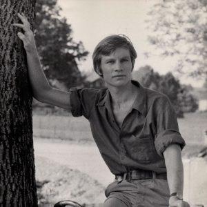 Michael York rides a bike, holds a tree.