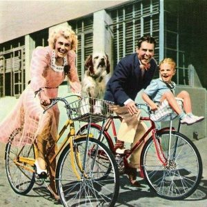 Penny Singleton, Daisy, Arthur Lake and Larry Simms ride bikes.