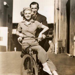 Ann Harding and costume designer Bernard Newmann ride a bike.