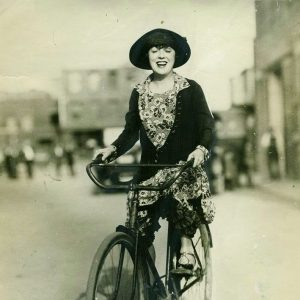Mabel Normand rides a bike.