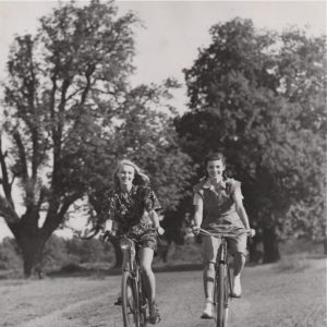 "Susan Shaw and Patricia Owen ride bikes.""HOLIDAY AT HOME"" == SUSAN SHAW and PATRICIA OWEN, under contract to the J. ARTHUR RANK ORGANIZATION, spent their holidays this year at home. Here they are, cycling through Richmond Park, Surrey."