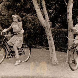 Lynn Merrick and Bob Crosby ride bikes, carry fan mail.