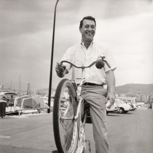Rock Hudson rides a bike, wheelie style.