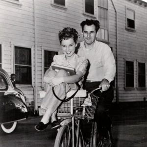 Janet Leigh and unidentified MGM crew guy ride a bike.