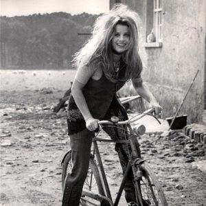 Senta Berger rides a bike.