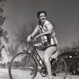 Gail Patrick rides a bike, Palm Springs, Calif., 1942.BICYCLING IS FUN… Smooth desert roads and sleepy village streets are great fun on a bicycle. Gail Patrick wears beige knee-socks, red and white striped bag and red shoes. Some ladies don't like slacks, and abhor shorts. The divided skirt if the solution. – MGM, 1942