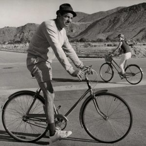 Walter Matthau and Lucy Saroyan ride bikes. Palm Springs, Calif., 1967.