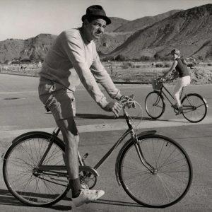 Walter Matthau and Lucy Saroyan ride bikes. Palm Springs, Calif., 1967.