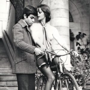 Tina Aumont rides a bike,  Alessandro Momo tries to get a grip.