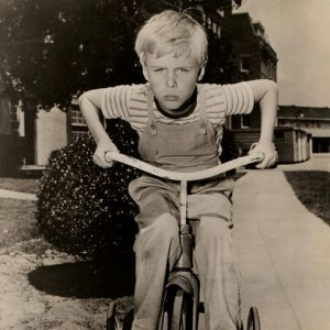 Jay North rides a trike.