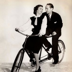 Joan Bennett and Franchot Tone ride a bike.