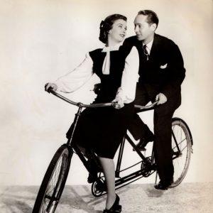 Joan Bennett and Franchot Tone ride a bike.