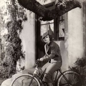 Joan Crawford rides a bike.