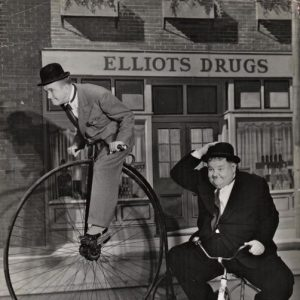 Stan Laurel and Oliver Hardy ride bikes.
