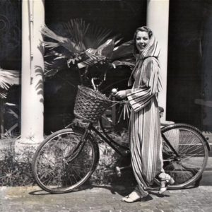Loretta Young walks a bike.