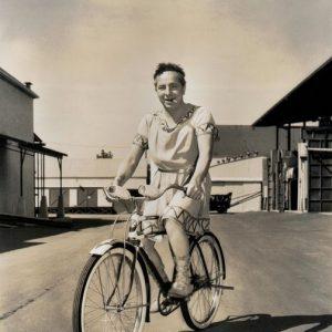 Joe Penner rides a bike, smokes a cigarette, wears a toga.