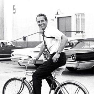 Paul Newman rides a bike.