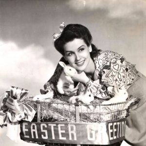 """Unidentified actress and unidentified bunnies ride an """"Easter Greetings"""" bike."""