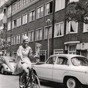 Elly Koot rides a bike, wields the 1964 Miss Europe trophy.