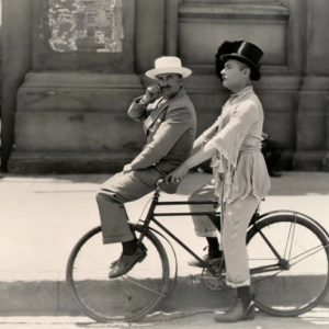 Roy D'Arcy and Lew Cody ride a bike.