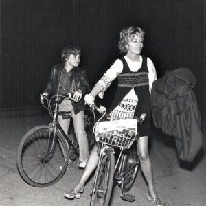 Steven Paul and Susannah York ride bikes.