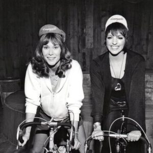 Kate Jackson and Liza Minnelli ride bikes, wear Campy casquettes.