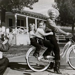 Betty Grable, Victoria James and Jessica James ride a bike. Harry James snaps a photo. Happy Mother's Day from Rides a Bike!
