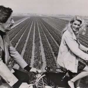 Jean Rochefort and Catherine Deneuve ride bikes.