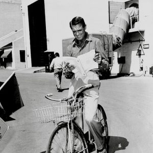 Cary Grant rides a bike, reads a script.