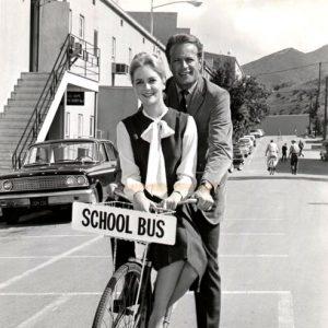 Katherine Crawford and Jason Evers ride a bike.