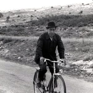 Fernandel rides a bike.