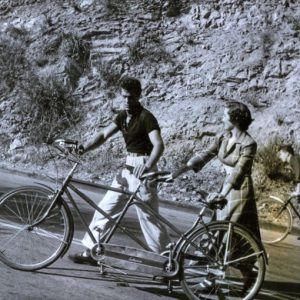 Tony Curtis and Colleen Townsend walk a tandem uphill.